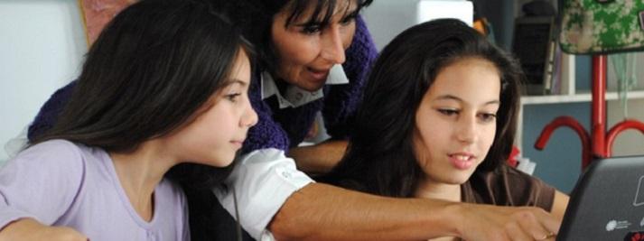 Fotografía en la que una madre y dos hijas miran una netbook