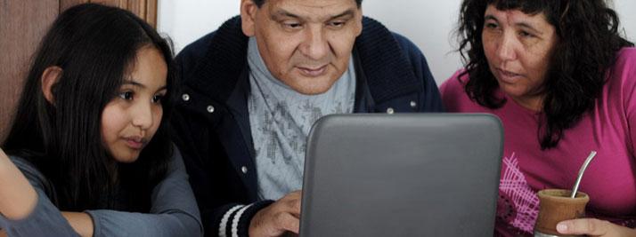 Un papá, una mamá y su hija pequeña observan atentos la pantalla de una netbook, en su casa. En color.