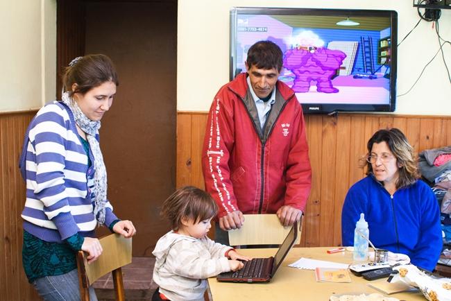 Dos mujeres y un hombre adulto, alrededor de una niña pequeña con una notebook. Están la habitación de una casa, donde hay una TV prendida de fondo a la escena. En color.