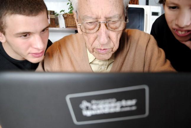 Un abuelo y sus dos nietos leyendo en una netbook. En color.