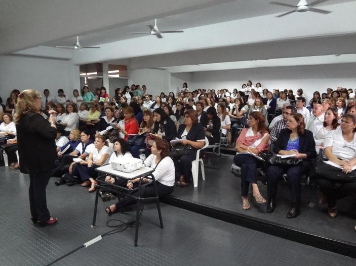 Multitud reunida en un salón escuchando a una persona con micrófono