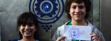 Un chico y una chica sostienen y muestran un dibujo de su invención. En color.